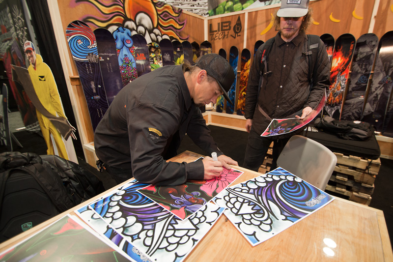Jamie Lynn signs posters featuring his original artwork that appears on his signature Lib Tech boards.